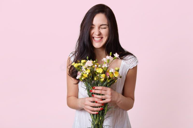 白色sundress的女孩享用花和恳切地笑气味,享受在桃红色背景的了不起的春日,摆在与 库存图片