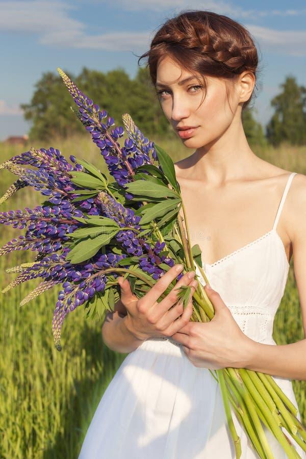 白色sundress的美丽的性感的妇女与花束在羽扇豆的手上在领域的在日落 库存图片