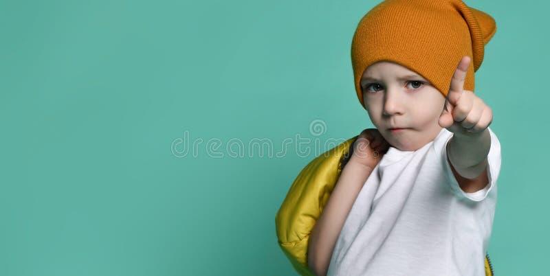 白色T恤、帽子和夹克的逗人喜爱的小男孩在他的摆在青绿的墙壁前面的手上 库存照片