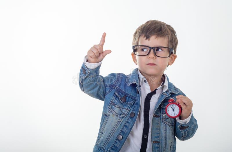 白色T恤和牛仔裤夹克的愉快的年轻男孩和看想出与红色时钟的指向手指在白色背景 免版税库存照片