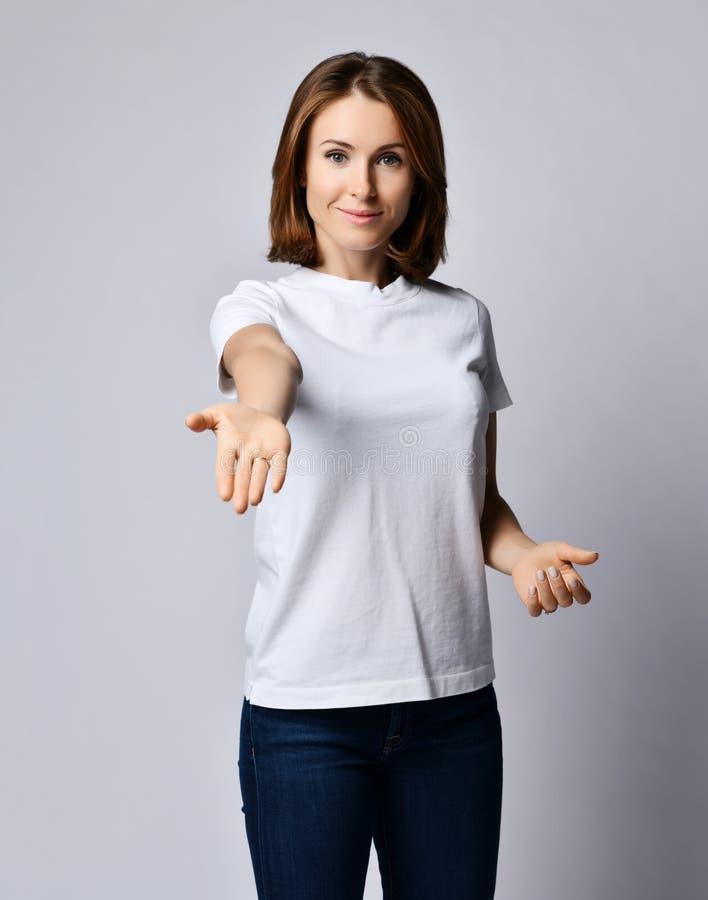 白色T恤和蓝色牛仔裤的好微笑的妇女握她的有开放棕榈的手象出去帮助或给我们某事 库存照片