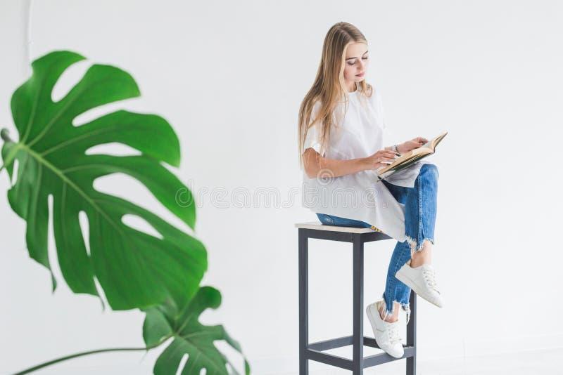白色T恤和蓝色牛仔裤的读书的一个年轻时髦的白肤金发的女孩的画象在白色背景 库存图片
