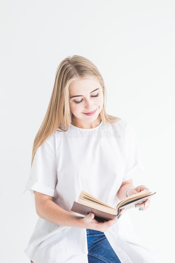 白色T恤和蓝色牛仔裤的读书的一个年轻时髦的白肤金发的女孩的画象在白色背景 库存照片
