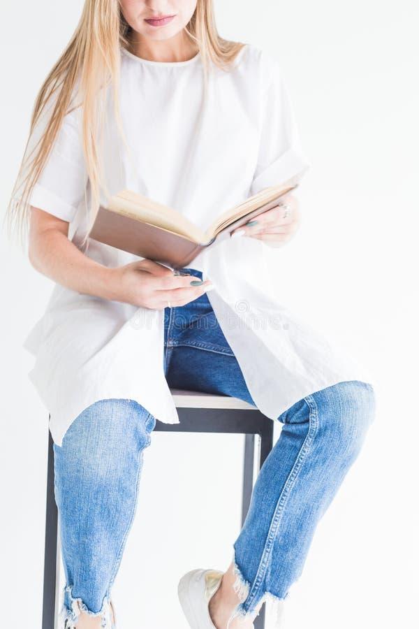 白色T恤和蓝色牛仔裤的读书的一个年轻时髦的白肤金发的女孩的画象在白色背景 免版税库存图片