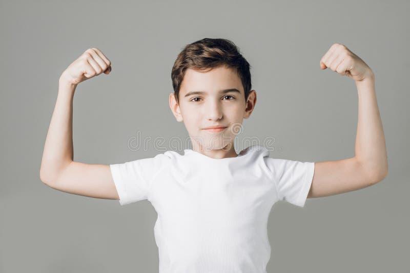 白色T恤在灰色背景隔绝的展示二头肌的逗人喜爱的好男孩 库存照片