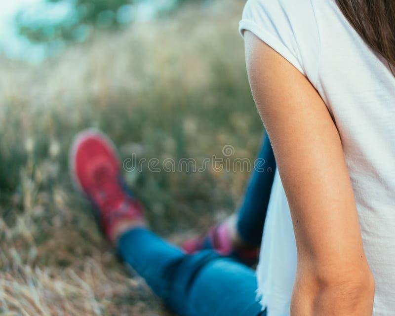 白色T恤杉、蓝色牛仔裤和红色运动鞋的女孩坐Th 免版税库存照片