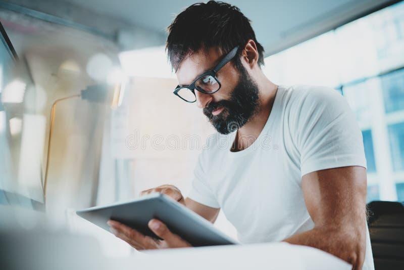 白色T恤杉佩带的眼睛玻璃和使用的便携式的电子赞成片剂计算机有胡子的人在现代lightful 免版税库存图片