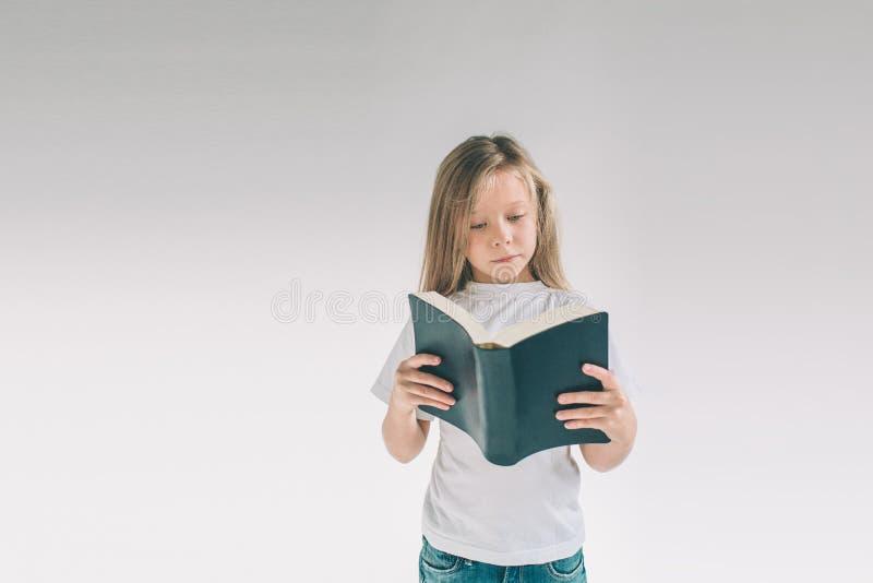 白色T恤杉的女孩在白色背景读一本书 书儿童节假日喜欢读 免版税库存图片