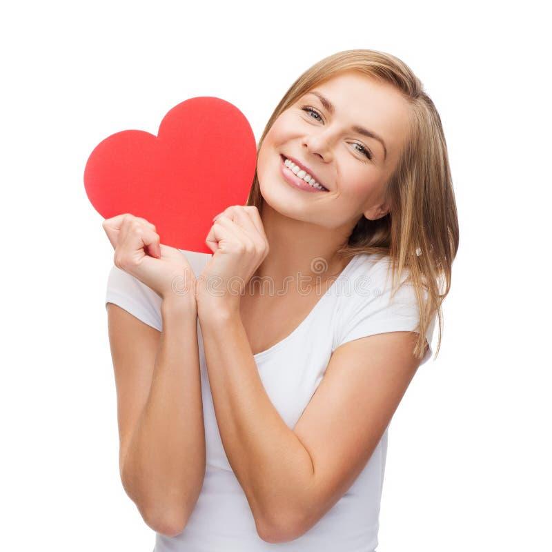 白色T恤杉的微笑的妇女有心脏的 库存图片
