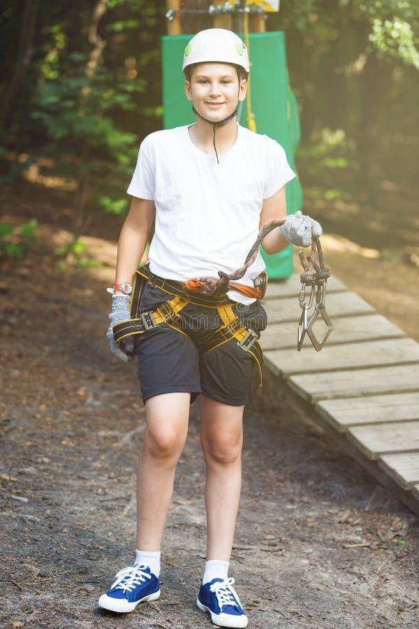 白色T恤杉的愉快,逗人喜爱,年轻获得乐趣和使用在冒险公园的男孩和盔甲, 图库摄影