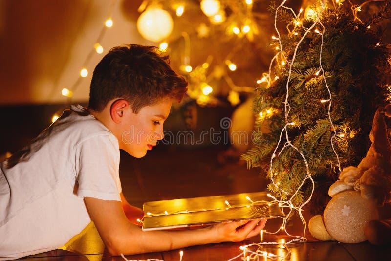 白色T恤杉的逗人喜爱的年轻男孩在家读书晚上在与光的杉树前面 寒假,新年 免版税库存照片