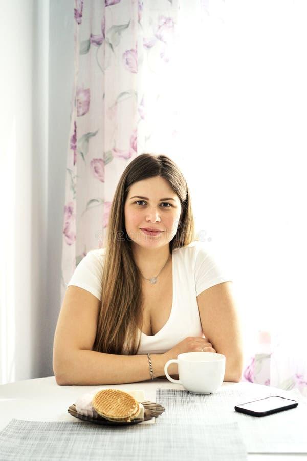 白色T恤的一名年轻长发白肤金发的妇女喝茶 免版税图库摄影