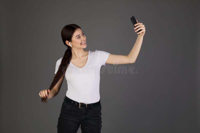 白色T恤的可爱的深色的女孩在灰色背景,看手机微笑 库存图片