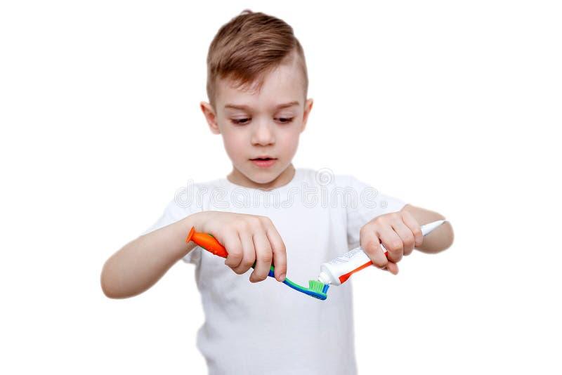 白色T恤的小男孩挤在刷子的牙膏 医疗保健、卫生学和童年概念 龋预防 免版税图库摄影