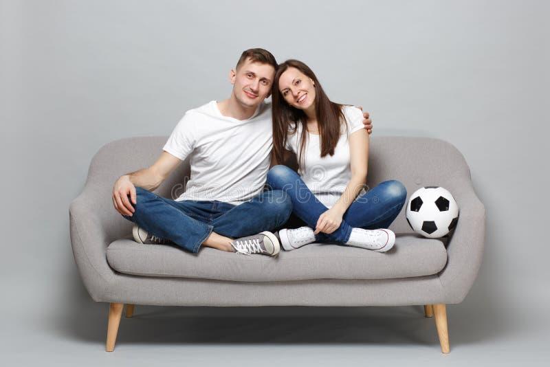 白色T恤的微笑的夫妇妇女人足球迷使与足球的支持喜爱的队振作,拥抱 免版税库存图片