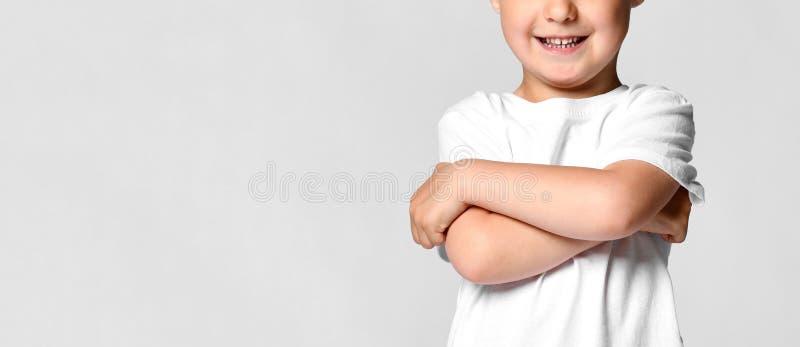 白色T恤的美丽的小男孩孩子,对他的胳膊横渡和微笑负,站立在白色背景 图库摄影