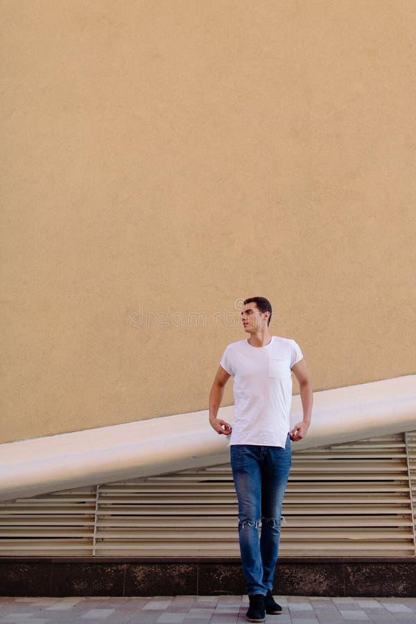 白色T恤的美丽的白种人人和蓝色牛仔裤在街道上停留 库存照片