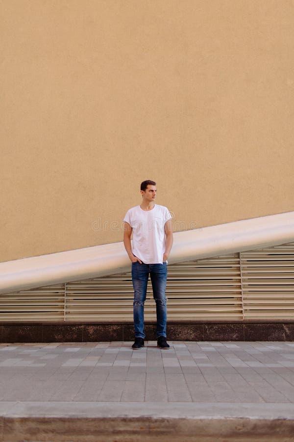 白色T恤的美丽的白种人人和蓝色牛仔裤在街道上停留 图库摄影