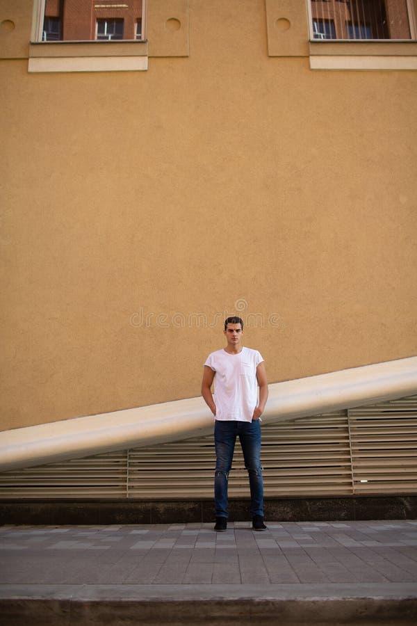 白色T恤的美丽的白种人人和蓝色牛仔裤在街道上停留 免版税库存图片
