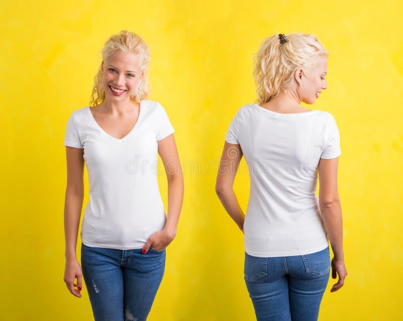 白色V脖子T恤杉的妇女在黄色背景 免版税库存照片
