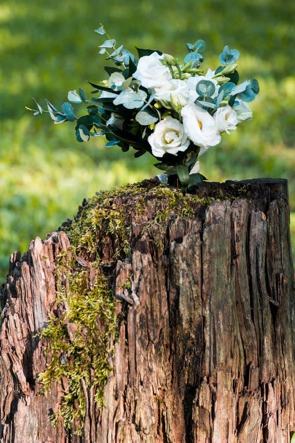 白花婚礼花束在户外木树桩的 库存照片