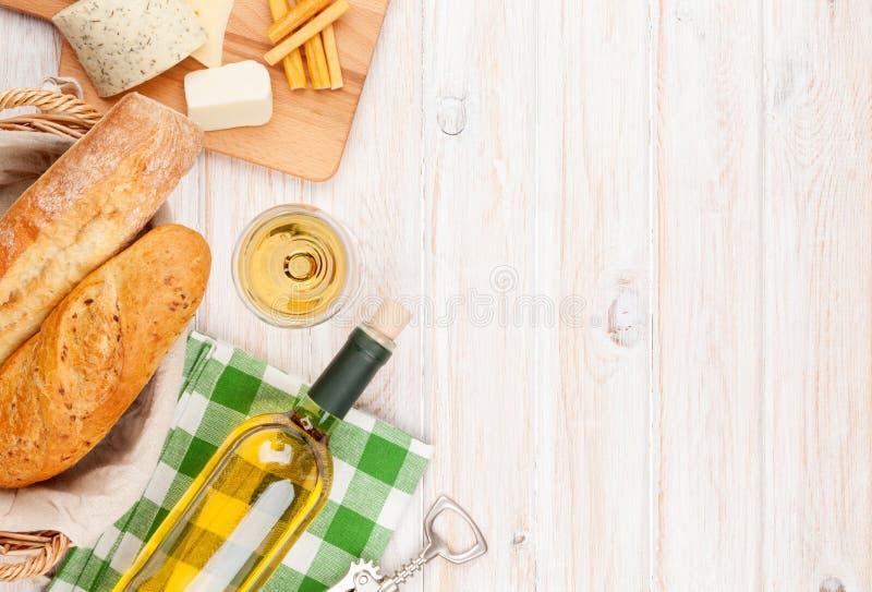 白葡萄酒、乳酪和面包在白色木桌背景 免版税图库摄影