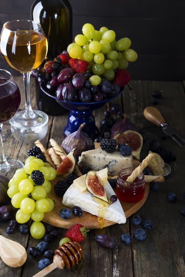 白葡萄酒、葡萄、面包、蜂蜜和乳酪 免版税图库摄影