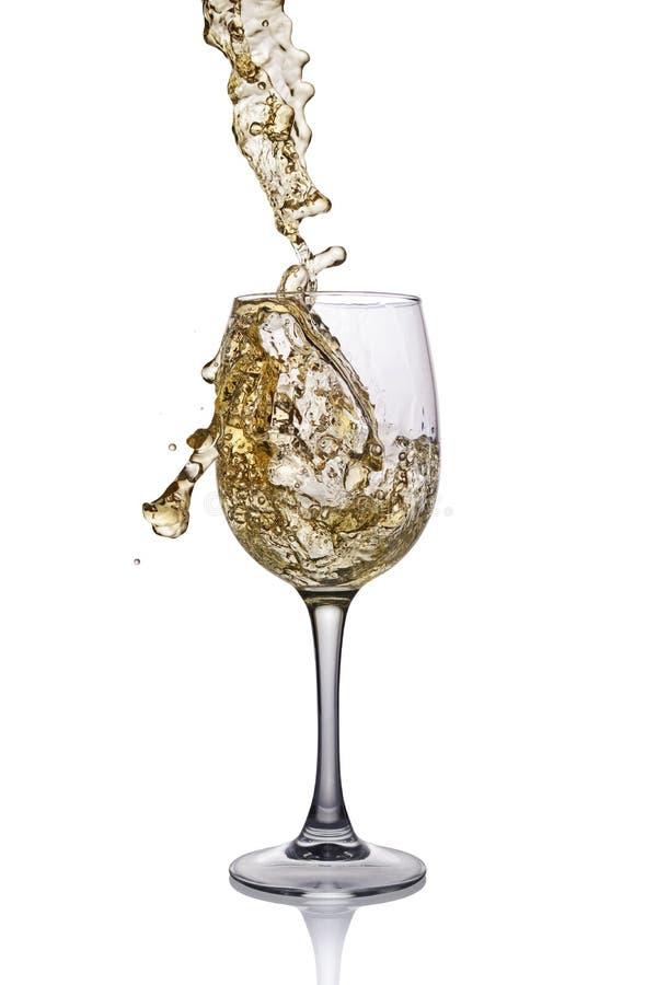 白葡萄酒飞溅在玻璃的与反射 免版税库存照片