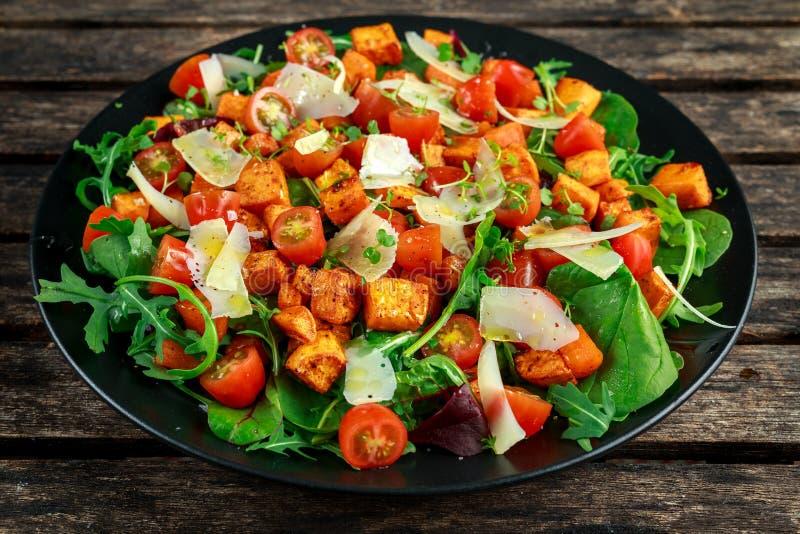 白薯、红萝卜、西红柿和狂放的火箭沙拉用希腊白软干酪在黑色的盘子服务 免版税库存图片