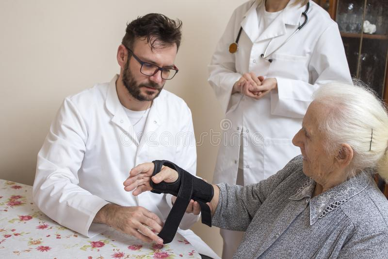白被剥皮的护士在医生的监督下使用在一个老妇人的腕子的一台安定器 库存照片