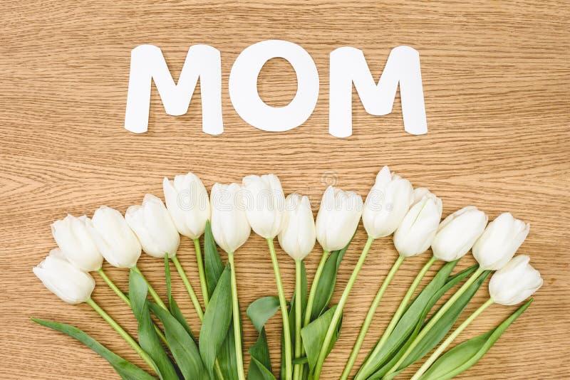 白郁金香和词妈妈顶视图在木桌,母亲节概念上 免版税图库摄影