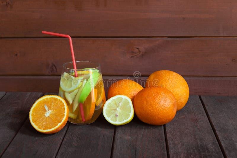 白酒桑格里酒用在玻璃和新鲜水果的果子在年迈的木桌上附近 免版税库存照片