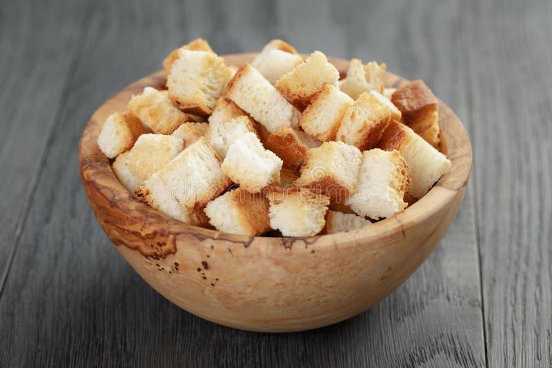 从白面包的自创油煎方型小面包片在木碗 免版税库存图片