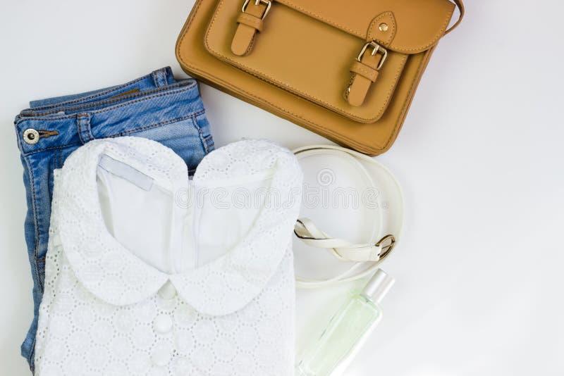 白鞋带妇女的女衬衫、蓝色牛仔裤、一个棕色提包和一条白色传送带在白色背景 妇女的偶然成套装备 r 库存照片