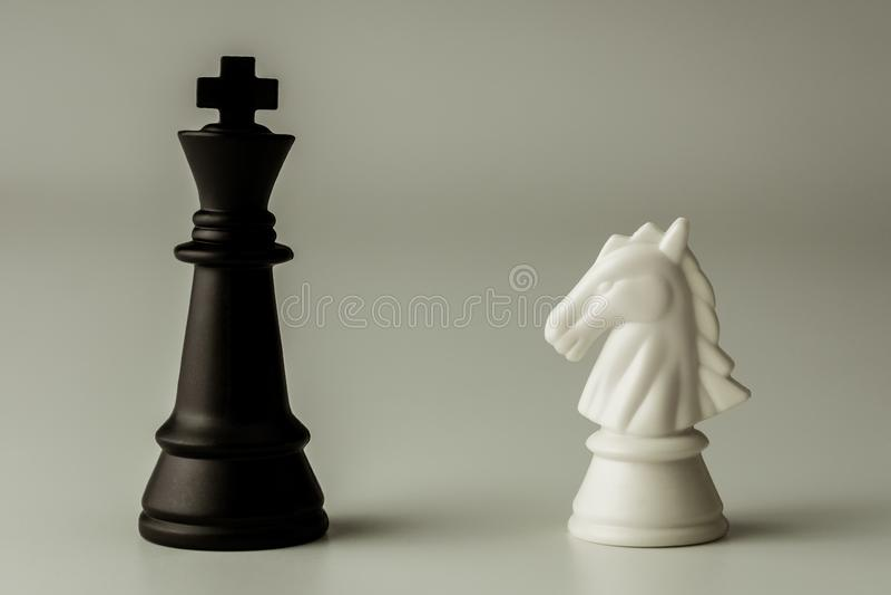 白马棋和黑国王棋立场遭遇在棋枰 - 企业优胜者和战斗概念 库存照片