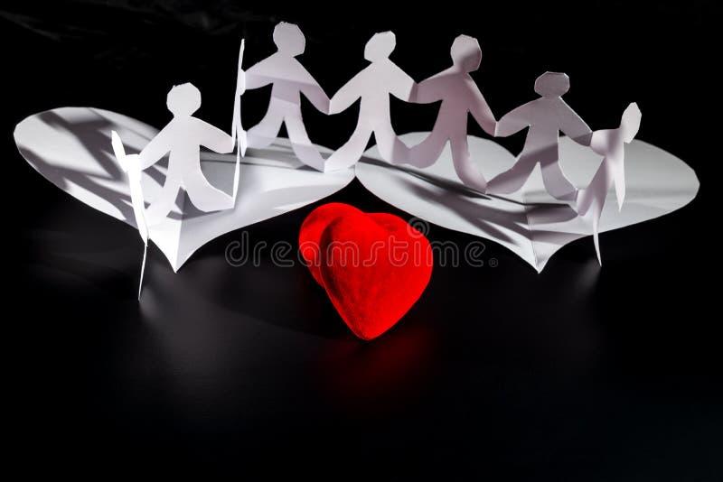 白origami人民在红心的白色origami翼飞行 国际人的团结天 库存照片