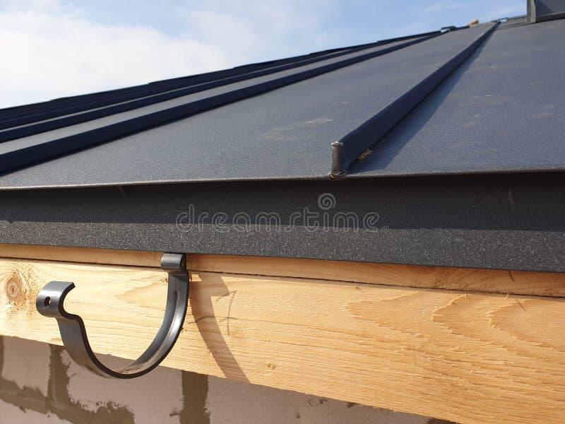 百叶窗排水系统支架在建房屋折顶的近景 免版税库存照片