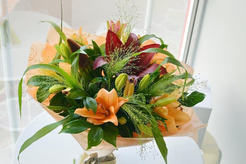 百合五颜六色的花束在橙色标度的 库存照片