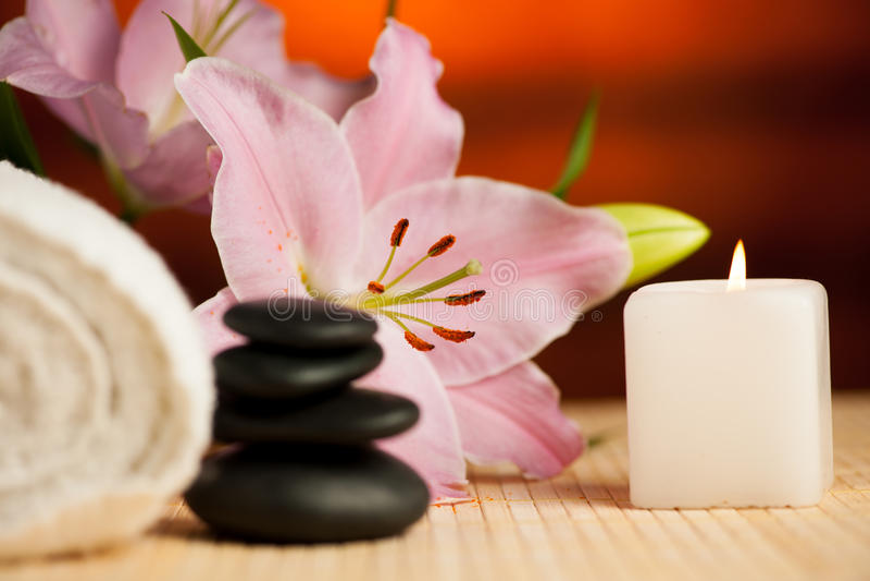 百合花、毛巾、海盐、蜡烛和水晶的温泉概念 免版税图库摄影