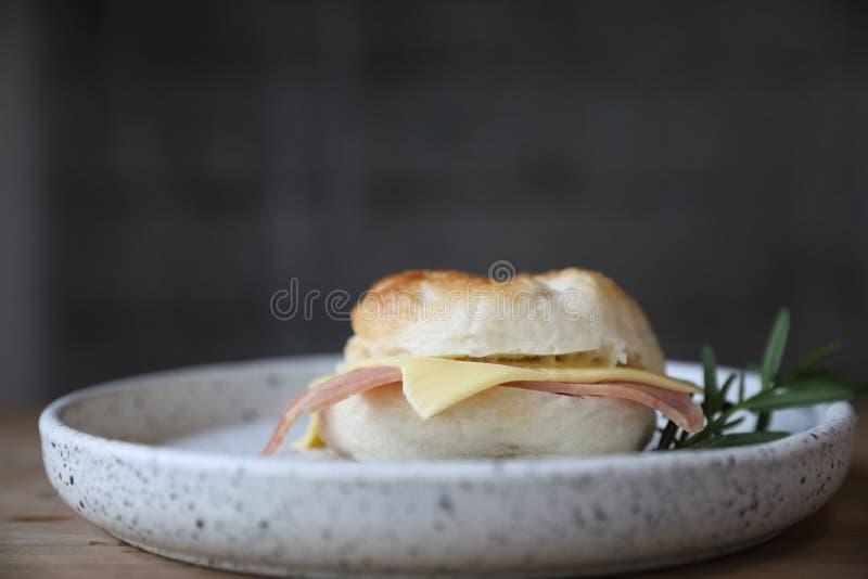 百吉卷在关闭的火腿乳酪在木桌上在咖啡馆 库存图片