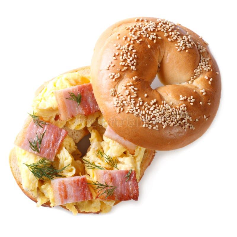 百吉卷用在白色隔绝的炒蛋和烟肉 免版税库存照片