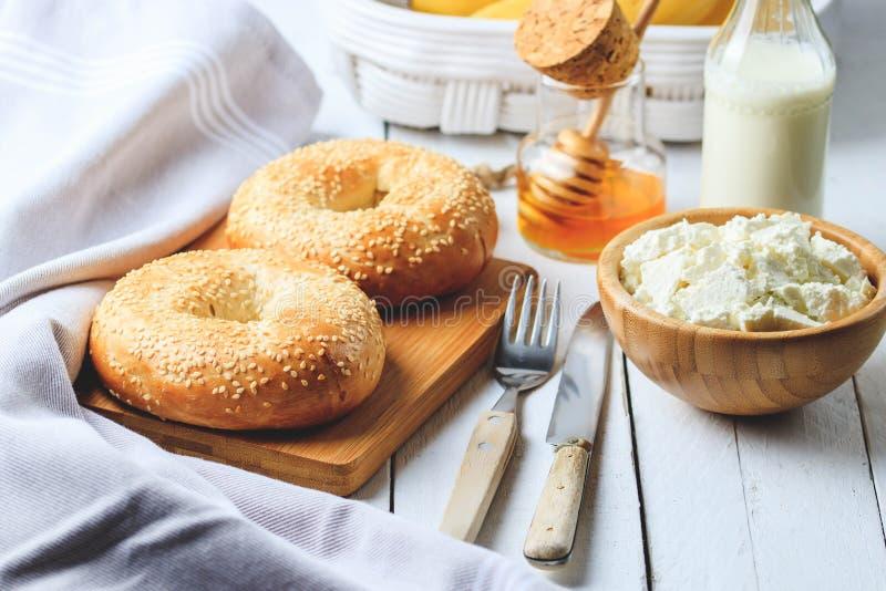 百吉卷用酸奶干酪、香蕉和蜂蜜 健康早餐白色木背景的概念 图库摄影