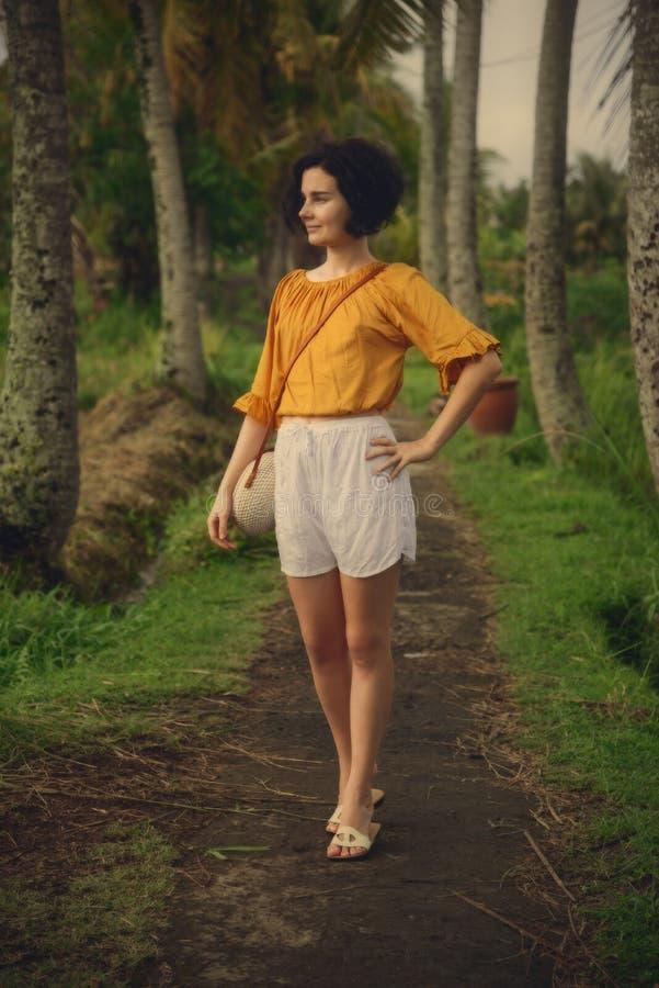的一个女孩在道路的白色短裤棕榈树之间 巴厘岛旅行 旅行,冒险 图库摄影