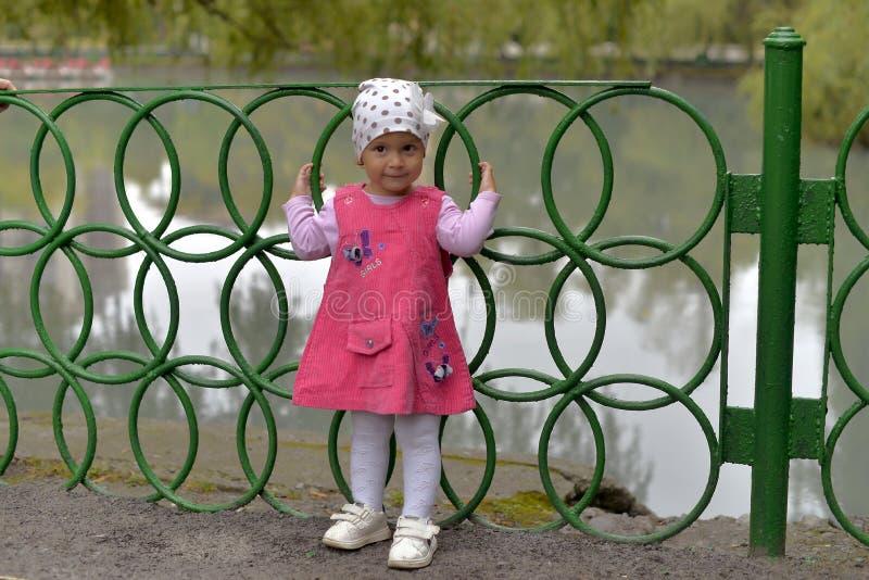 的一个小女孩桃红色sundress和一个白色盖帽站立在篱芭 库存照片
