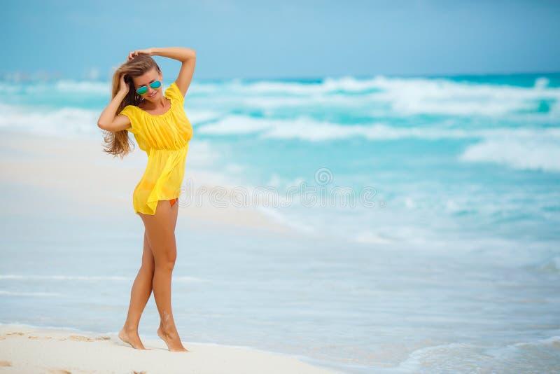 的一名妇女在一个热带海滩的黄色sundress 免版税库存图片