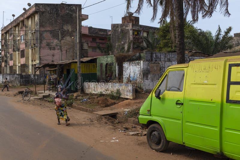 的一名妇女比绍的街道有居民住房的在背景,在几内亚比绍 免版税库存照片