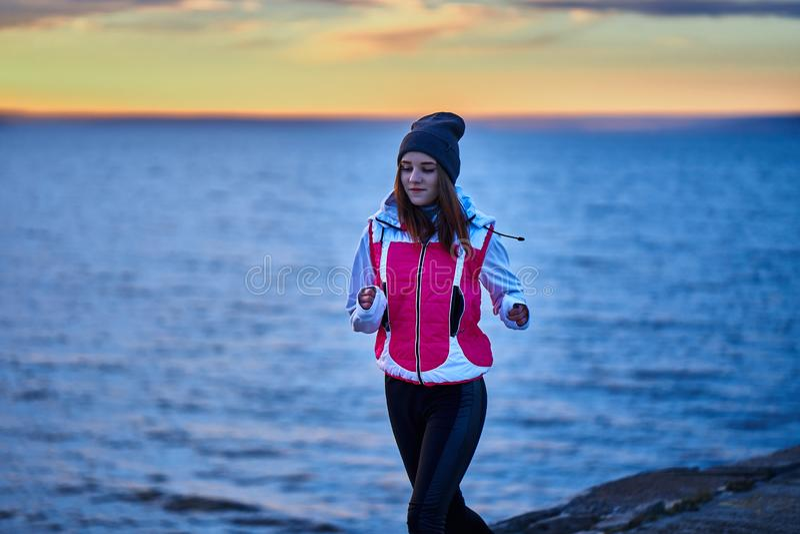 的一少女体育帽子和夹克在堤防做早晨凹凸部早晨在太阳的黎明前 免版税库存照片