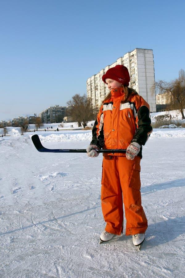 的一微笑的女孩橙色总体在冰鞋的一溜冰场在她的手上站立并且拿着一根曲棍 图库摄影
