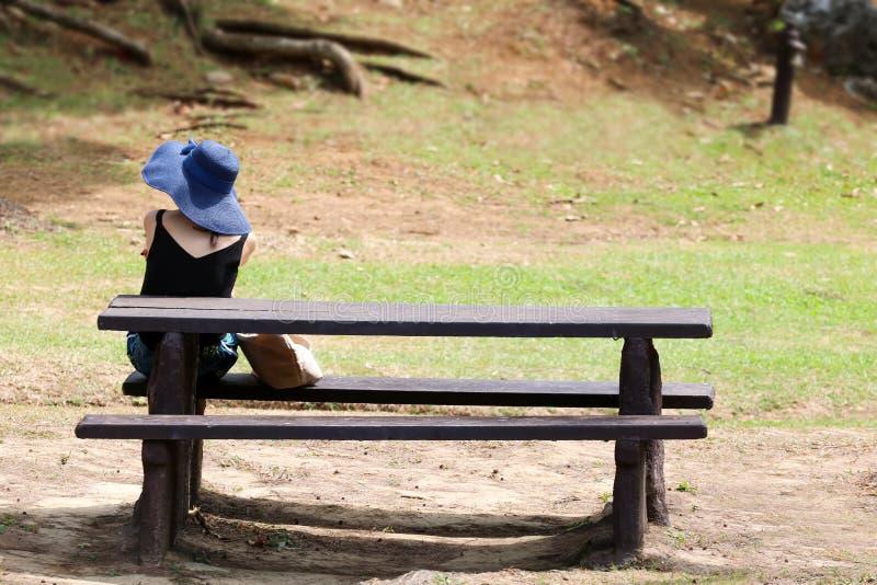 的亚裔妇女或等待坐在pa的一条长凳的后面观点 图库摄影
