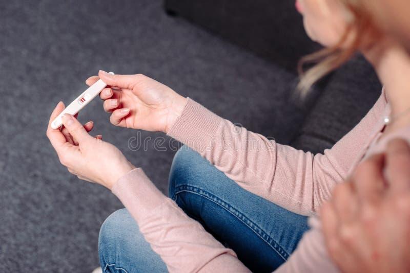 的人拥抱有妊娠试验的部份观点妻子 免版税库存图片